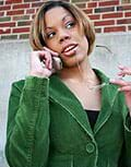 Photo shows a young woman talking on a cell phone.