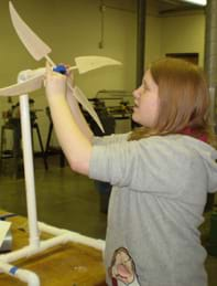 A young girl at a table attaches a 4-blade turbine to a PVC support stand.