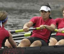 Photo shows three female high school rowers working hard as they pull on paddles to power a boat.
