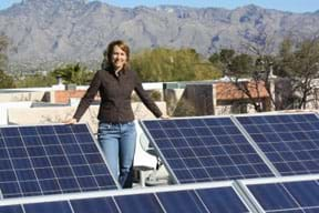 Photo shows a woman standing amidst dark blue angled solar panels on a city rooftop with a blue sky and mountain backdrop.