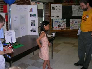 In front of a posterboard, a student describes her energy project to an adult.