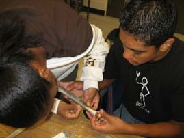 Photo shows two students holding and taping a six-inch bone.