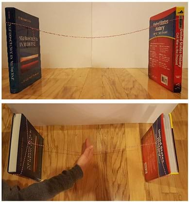 Two photographs: A side view shows two text books standing up vertically about 18 inches apart, with one long string tied around one book, strung across the gap and then tied around the second book. A view from above of the same setup shows a hand pressing down on the middle of the string across the gap between the two books, which results in the books both falling inwards.