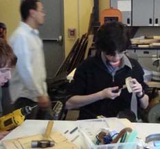 Photo shows a student at a classroom workbench attaching the heel to a shoe.