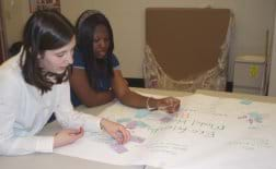 Two students at a table look at project solution ideas written on a large sheet of paper and applied sticky notes.