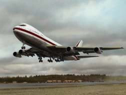 Photo shows a large streamlined airplane lifting off from a runway.