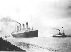 Black and white photo shows a big ship with four smokestacks moving through the water.