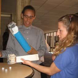 Photo shows two people at a table with forearm prostheses made from boards, eyelet screws, fishing line, plastic tubing and duct tape to make crude hands with fingers, tossing dice.