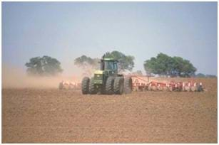 Photo shows a large green tractor with eight wheels pulling a very wide disc plow in a dusty field.