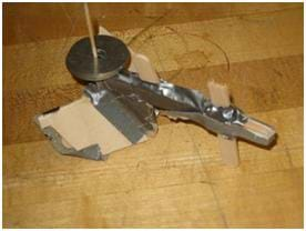 Photo shows a rudimentary model plow made from thin pieces of wood and duct tape.
