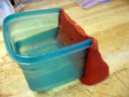 Photo shows a wedge of red clay that has replaced one side of a small plastic container, with the container filled with water to show that it holds water.