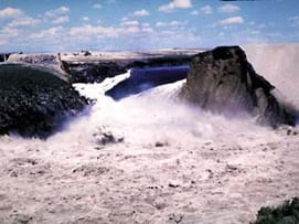 Photo shows water gushing through a break in the wall of a dam.