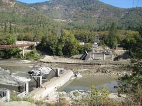 Photo from a riverside shows a concrete dam, half removed from blocking a river, with water flowing through the unobstructed side.