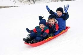 Three young boys on a sled playing in the snow.