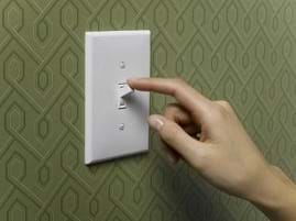 A finger pressing an on/off switch.