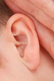 A close-up photograph of a person's ear and hand.