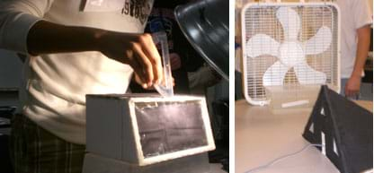 Two photos: A student uses a protractor to position the angle of a desk lamp shining on a box-shaped structure of foam core board with a plastic window wall. A box fan on a table blows air past a plastic container of ice towards a black foam core model house with a pitched roof, windows and a door.
