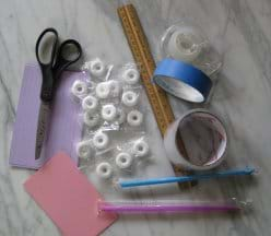Photo shows scissors, tape, ruler, straws, lifesaver-shaped white candies and index cards in a pile on a tabletop.