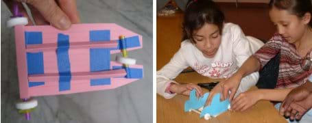 Two photos: (left) The undercarriage of a mint-mobile shows folded index cards and cut straws taped to form axles and structural support. (right) Two young girls work together using their hands to make a blue car made of paper, straws and lifesaver-shaped candies (for wheels).