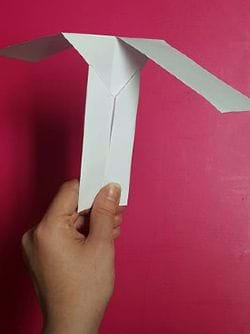 "A hand holds a simple ""helicopter"" made from cut and folded paper."