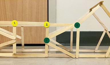 "A photograph shows the side view of a bridge truss structure made from wooden craft sticks hot glued together. It looks like a geometric web of sticks connected together to form various polygon shapes. Two small round yellow stickers, marked ""1"" and ""2,"" are placed at two adjacent corners of a square truss component composed of four sticks. Nearby, two small round green stickers, marked ""1"" and ""2,"" are attached to two adjacent corners of a triangle truss component. The stickers identify angles will be measured before and after load testing to check for deformation."