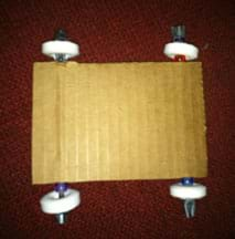 A photograph shows a view from above of two plastic coffee stirrers run through the cardboard layers of a 3 x 5 piece of corrugated cardboard, making axles in a car chassis base. Where the stirrers extend outside of the cardboard at four spots, wheels are attached by placement of a plastic bead and then ring-shaped hard candy, with the stirrer ends duct-taped.