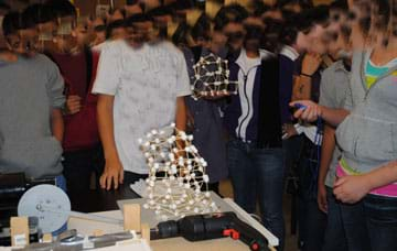 Photo shows many 8th grade students around a table, one holding a stopwatch, watching a marshmallow and toothpick structure move on an electronic mini shake table.