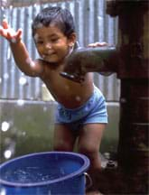 Photo shows a boy splashing water from a bucket under a steel water pump.