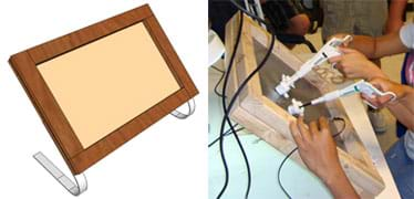 Two images: (left) Drawing shows a wooden frame around a latex rubber sheet with curved aluminum strips as support legs.(right) Photo shows two pairs of hands holding laparoscopic tools and a small digital camera, all inserted through slits in the framed rubber sheet.