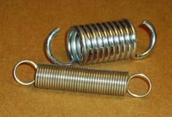 Photo shows two tension springs: a short and wide one made of thick metal and a longer, thinner one made of much thinner metal.
