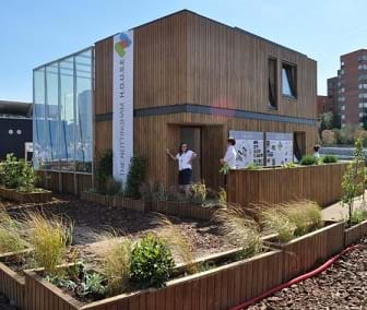 A photograph shows the Nottingham HOUSE (home optimising the use of solar energy) built as part of the Solar Decathlon 2010 event--a cube-shaped structure.