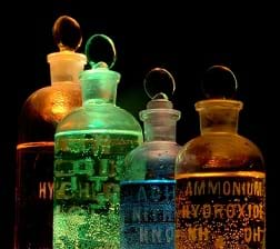 Four flasks containing different chemicals (including Ammonium hydroxide and Nitric acid) lit in different colors.