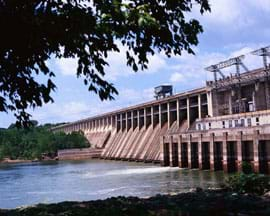 Photo shows a concrete dam blocking a river's passage.