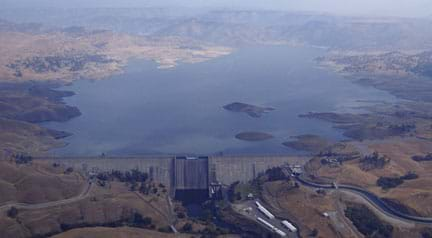 Aerial photo shows a wide and straight concrete structure blocking a river flow and holding back a supply of water. From above, the structure shape looks like a wall across the river width, tipped towards the resulting reservoir.