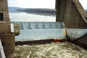 Photo shows a concrete and metal structure enclosing a section of a river.