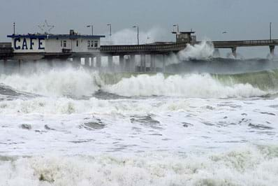 Violent and frothy waves splash around the walkway and columns of an ocean-side pier, as well as the shallow water near the shore.