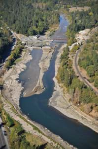 Aerial photo shows a narrow stream of water flowing unobstructed through one side of a river in which the concrete dam is gone while a bulldozer moves piles of dirt to block the water's passage through the remaining half of the dam.