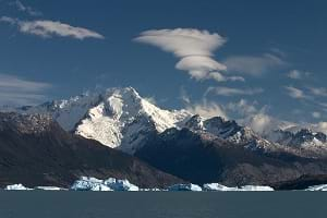 A photograph shows a huge snow-capped mountain with water in the foreground—the Andean range over the Santa Cruz province and Lake Argentino.