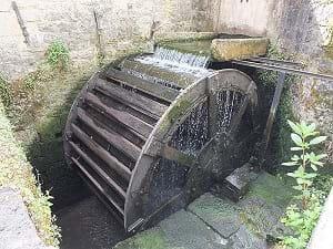 An overshot waterwheel showing water flowing through it in Goyet, Beligum.