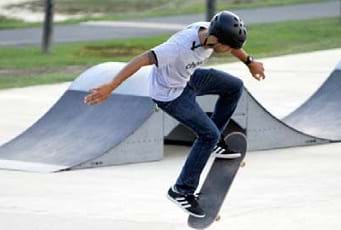 A skateboarder doing a trick in midair.
