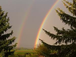 A photograph shows a double rainbow in the sky.