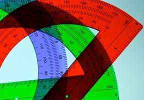 A photograph shows three overlapping translucent plastic protractors of different colors, blue, green and red. The devices are semi-circular in shape. Markings show inches and degrees.