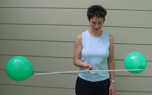 Photograph of a woman holding a meter stick, with inflated balloons attached on each end, perfectly balanced on one finger.