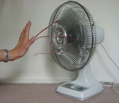 Photograph of a person's hand feeling the moving air in front of a running electric table fan.