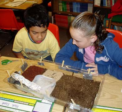 Photo of a boy and a girl looking at the sand, soil, bark, and water pool in the base of their model biodome.