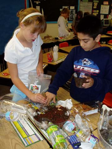 Two students place soil in their plastic biodome base.