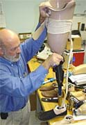Photo shows man assembling prosthetic leg that has a hydraulic knee system.