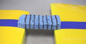 Photo shows a sponge with eight parallel black lines drawn around it spanning two stacks of books ~3 cm above a table surface.