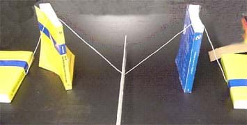 Photo shows a string M created by placing two books standing up and draping the string over the tops of them.