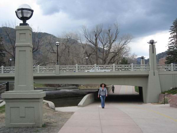 A concrete beam bridge spans a river and a pedestrian path.